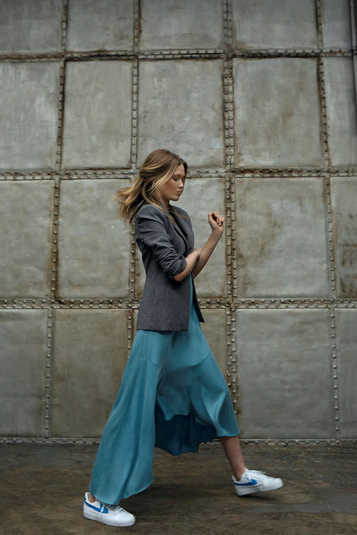 blue flowing dress, grey jacket, white trainers